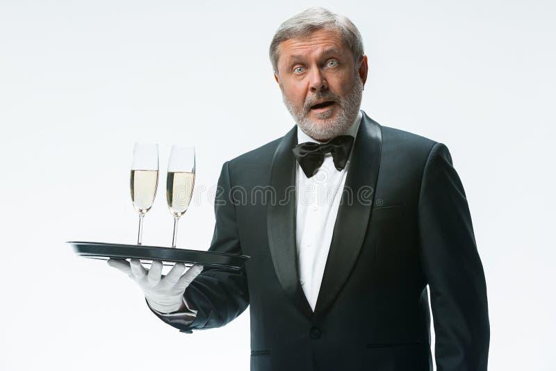 Le serveur professionnel dans l'uniforme sert le vin images libres de droits