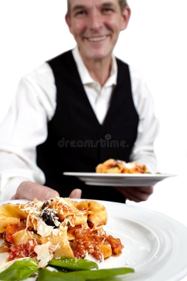 Le serveur sert des pâtes images stock