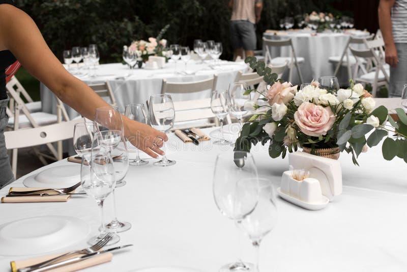 Le serveur sert la table de banquet Épousant l'arrangement de table décoré des fleurs et des chandeliers en laiton avec des bougi photographie stock libre de droits