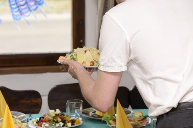 Le serveur sert une salade sur la table images stock