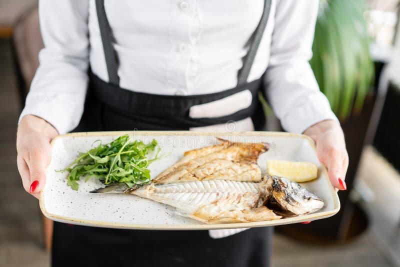 Le serveur tient une assiette de Dorado avec de l'arugula et du citron Les fruits de mer BBQ Menu Restaurant photos libres de droits