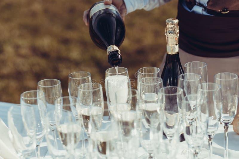 Le serveur verse le champagne en verres images stock