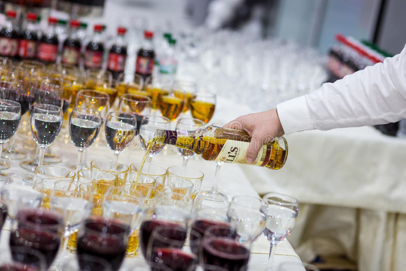 Le serveur verse le whiskey dans un verre verres sur le tabl blanc images libres de droits