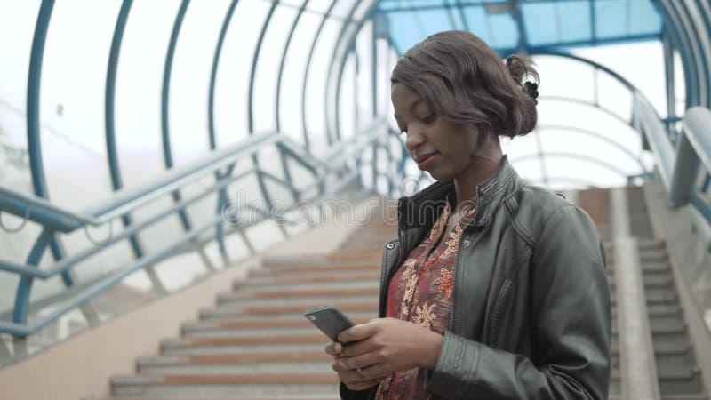 Le service de mini-messages mignon de fille d'Afro-américain au téléphone s'est occupé sur l'écran du comprimé, la femelle Afro,  photographie stock