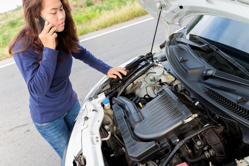 Le service de voiture de secours d'appel de femme après sa voiture a un ploblem photographie stock libre de droits