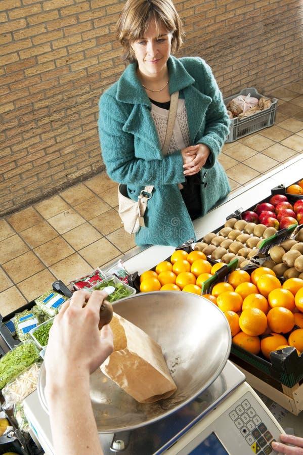 Le service du marchand de légumes photo stock