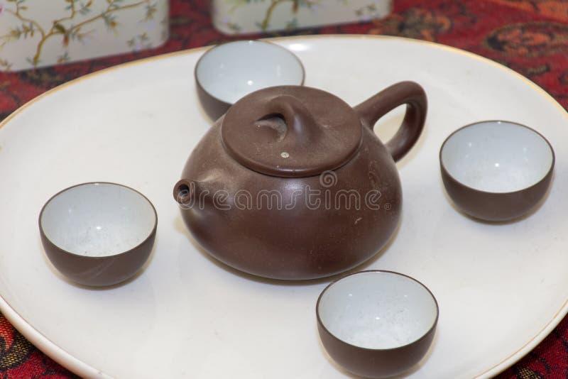 Le service ? th? chinois d'argile de Brown a ?tendu d'un plat blanc images libres de droits