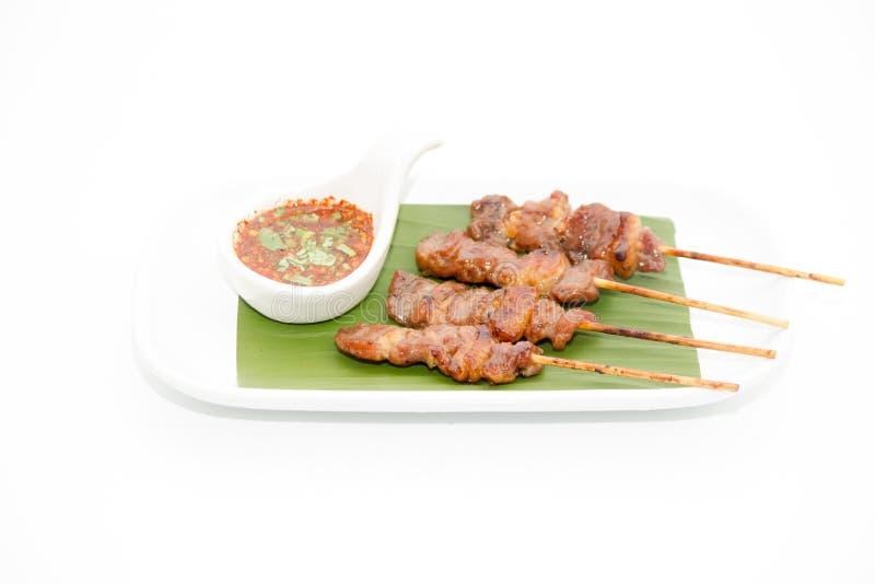 Le service thaïlandais de porc de BBQ avec et la sauce thaïlandaise à style ont placé sur la banane le photographie stock libre de droits
