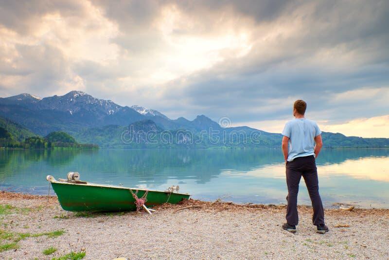 Le seul homme s'assied sur le banc près d'un lac azuré de montagne L'homme détendent images stock