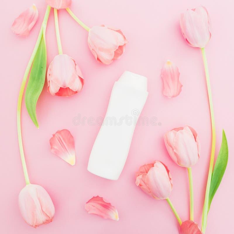 Le shampooing et les tulipes blanches fleurit sur le fond rose Configuration plate, vue supérieure photographie stock