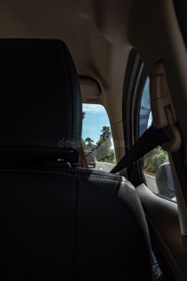 Le siège avant de la voiture et la vue de la route dehors ont regardé du siège arrière images libres de droits