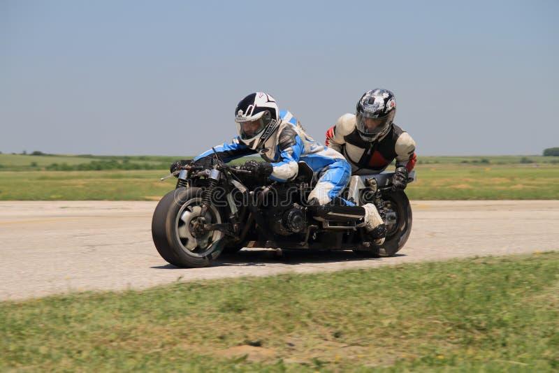 Le sidecar isolé de motocyclette dans virage à gauche dessus la voie photographie stock
