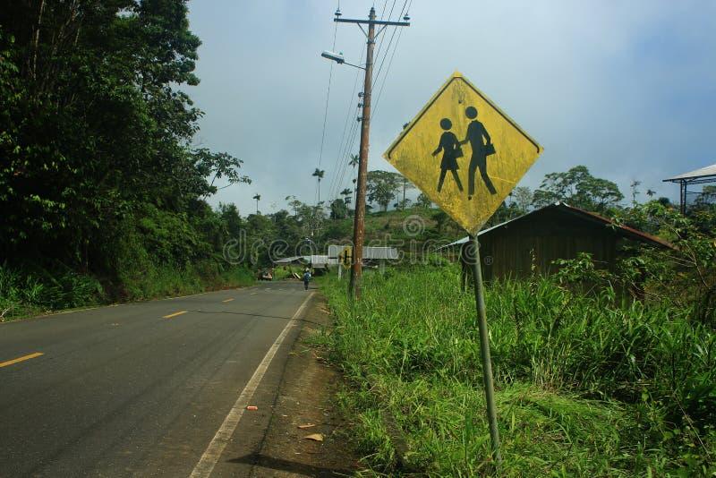 Le signe ? c?t? de la route dans un petit village indiquant qu'il y a une ?cole et les enfants pr?sentent photographie stock libre de droits