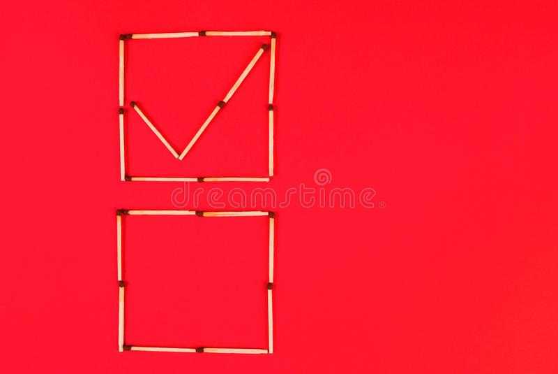 Le signe correct dans des cases à cocher et vident des matrices font des matchs sur le fond rouge photo stock