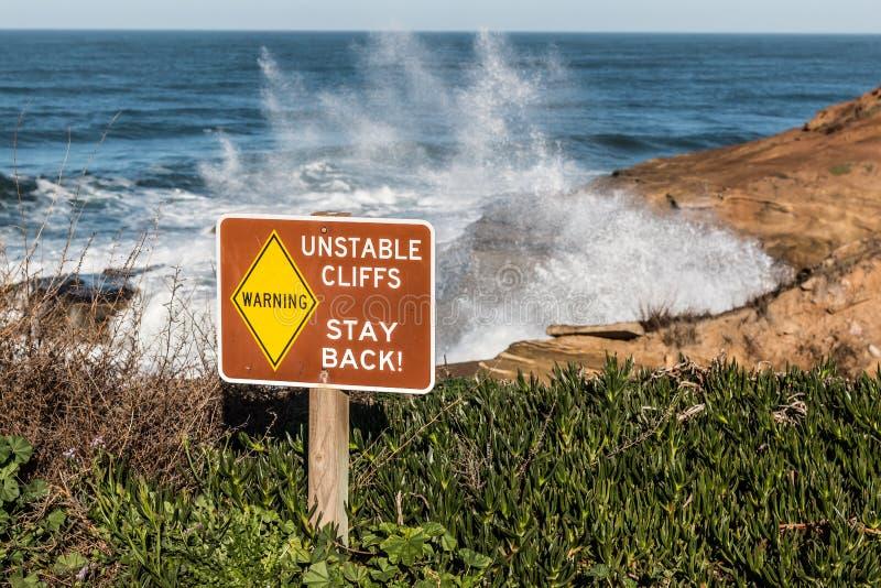 Le signe de danger avec se briser ondule aux falaises de coucher du soleil images libres de droits
