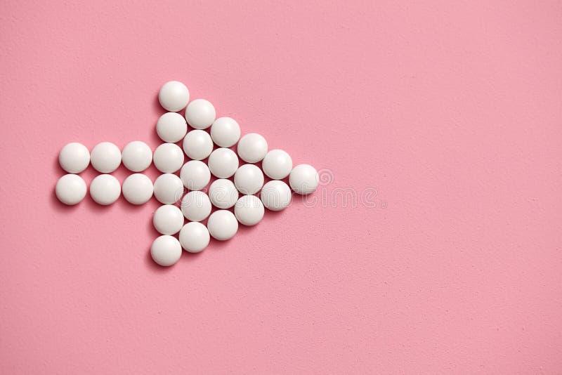 Le signe de flèche est garni des comprimés blancs et ronds sur un fond rose photo stock