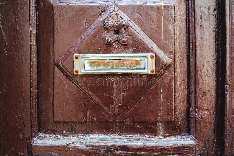 Le signe de lettre est un symbole de la boîte aux lettres attachée à la porte en bois brune de la maison Méthodes périmées de cor image libre de droits