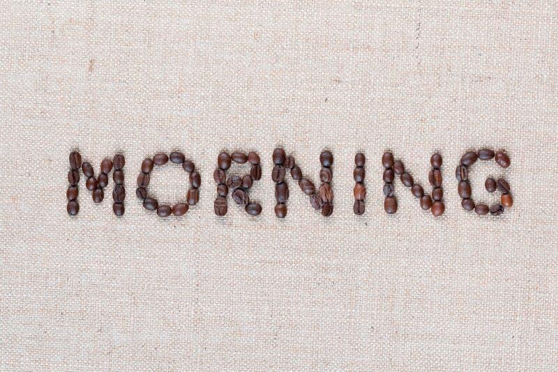 Le signe de lettre de matin des grains de café d'isolement sur la texture de linea, a tiré étroitement d'en haut images stock