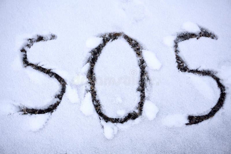 Le signe de SOS pour l'aide a eu besoin écrit dans la neige image stock
