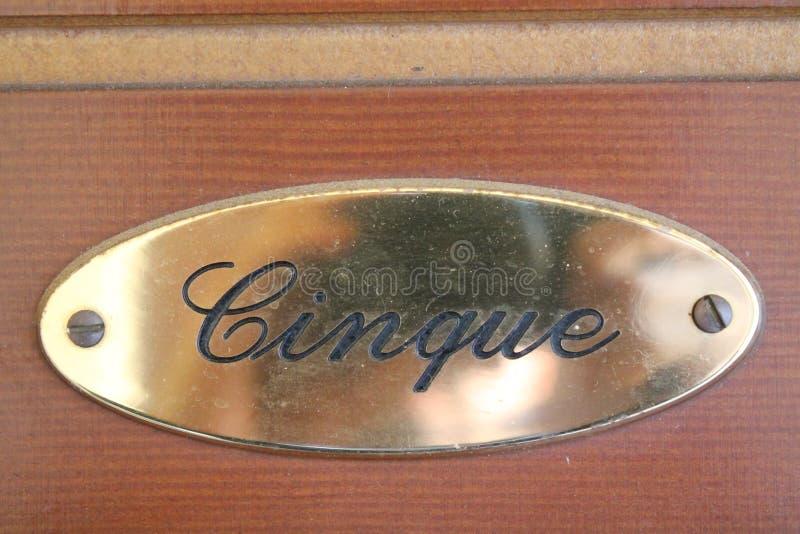 Le signe du numéro de maison 5 écrit en langue de l'Italie sur le brun a peint la porte en bois images libres de droits