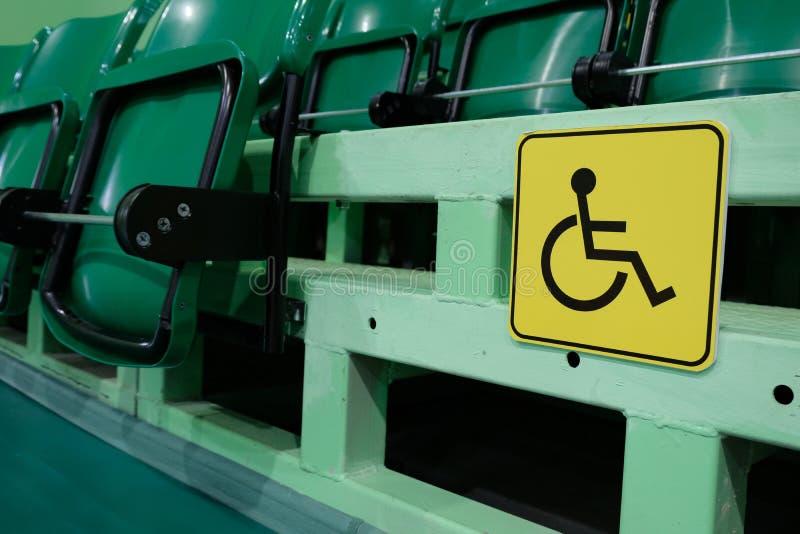Le signe jaune est un endroit pour des handicapés dans le gymnase parmi les sièges pour des spectateurs Amphithéâtre avec des ran images libres de droits
