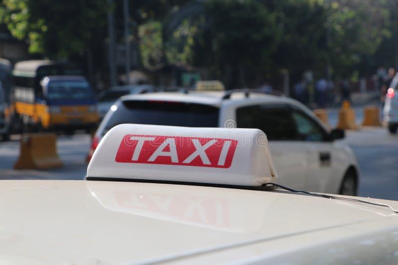 Le signe ou la cabine de lumière de taxi signent dans la couleur blanche et rouge avec le texte blanc sur le toit de voiture photos libres de droits