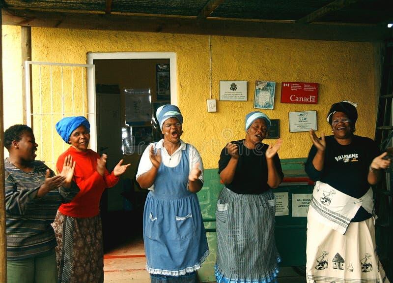Le signore cantano ed applaudono in un distretto nel Sudafrica immagine stock