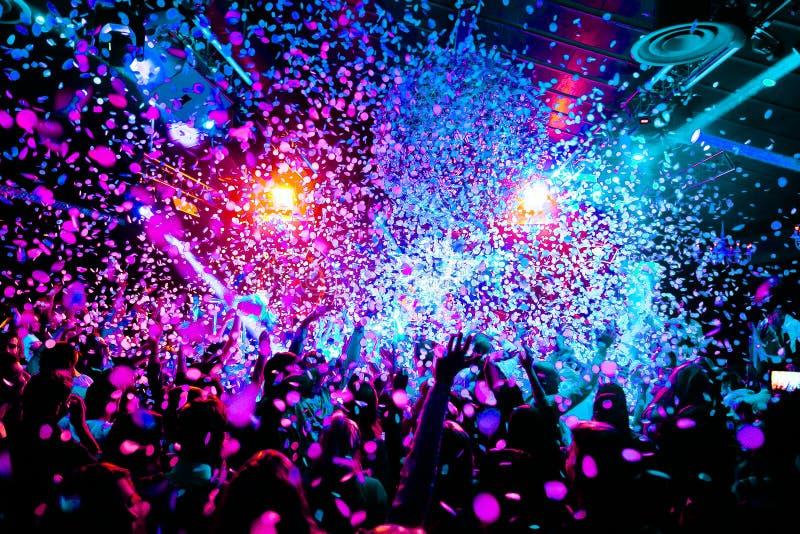 Le siluette del concerto ammucchiano davanti alle luci luminose della fase con i coriandoli immagini stock libere da diritti