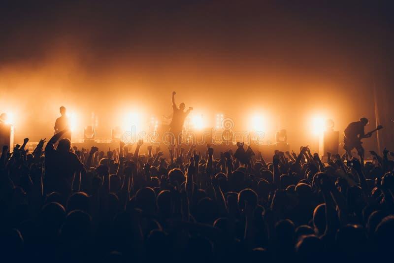 Le siluette del concerto ammucchiano davanti alle luci luminose della fase Una folla esaurita sul concerto rock Folla dei fan a m fotografie stock libere da diritti