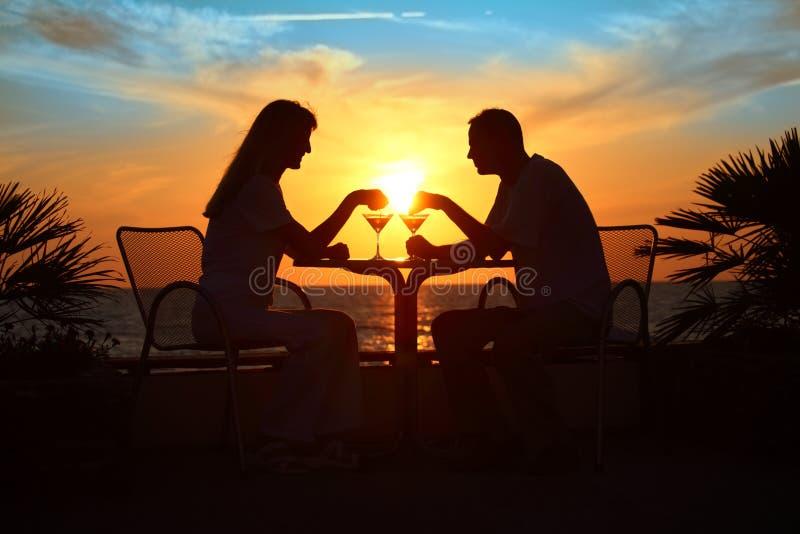 Le siluette della coppia sul tramonto si siedono alla tabella fotografia stock libera da diritti