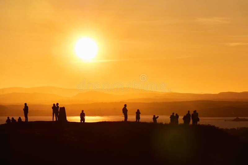 Le siluette umane che stanno su una collina davanti ad un sunseHuman dell'arancia profila la condizione su una collina davanti ad immagine stock