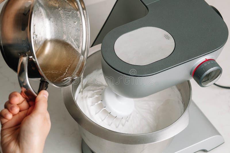 Le sirop de sucre d'agar est versé dans les blancs d'oeuf fouettés avec du sucre Le processus de faire la guimauve de guimauve da photos stock