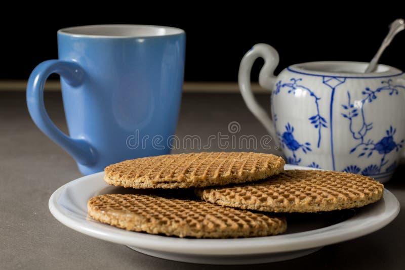Le sirop néerlandais délicieux waffles d'un plat blanc avec la tasse de café et de sucre photo libre de droits