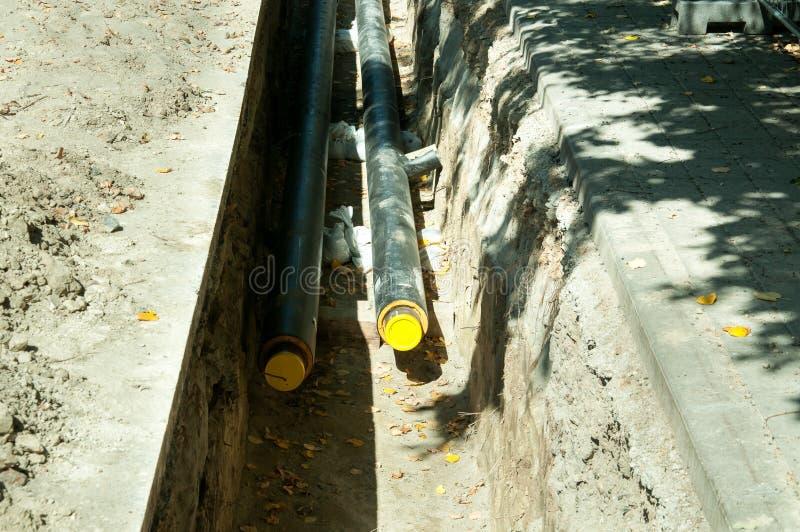 Le site d'excavation à remplacer la canalisation souterraine d'eau chaude en bas de la rue au quartier de la ville avant saison d photos stock