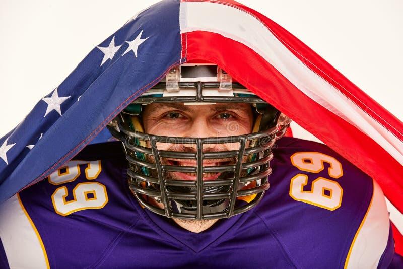 Le, skäggig amerikansk fotbollsspelare i likformign som täckas med en amerikanska flaggan N?rbild vit bakgrund arkivfoton