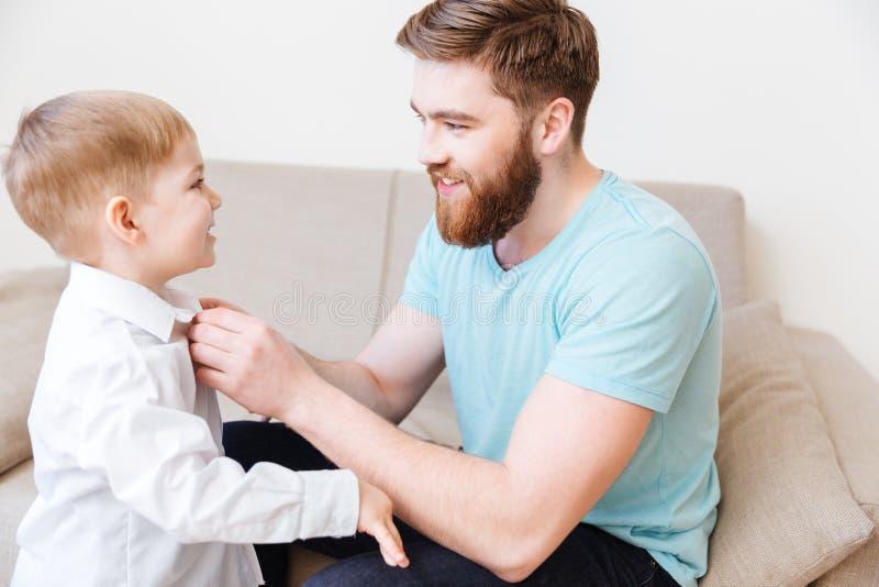 Le skäggigt barn avla att klä hans lilla son royaltyfria bilder