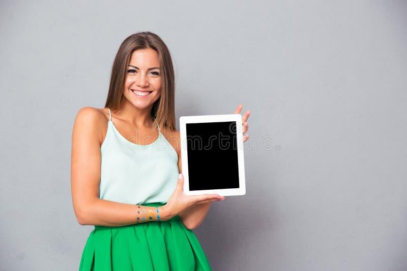 Le skärmen för dator för minnestavla för kvinnavisningmellanrum royaltyfri foto