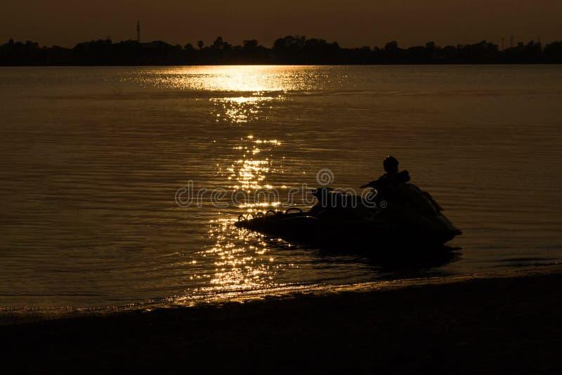 Le ski de jet avec le coucher du soleil dans la soirée et la lagune en Thaïlande image libre de droits