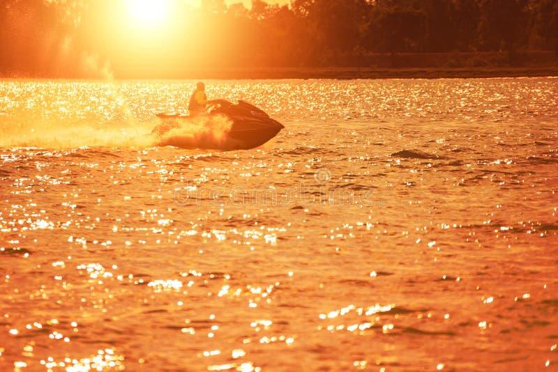 Le ski de jet est sur l'eau et le coucher du soleil de mer photographie stock