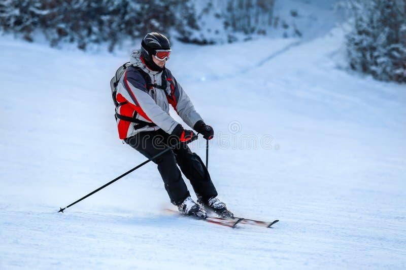 Le skieur dans le costume de ski glisse vers le bas de la pente de neige image stock