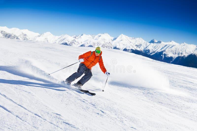 Le skieur dans le masque glisse rapidement tout en skiant de la pente photo libre de droits
