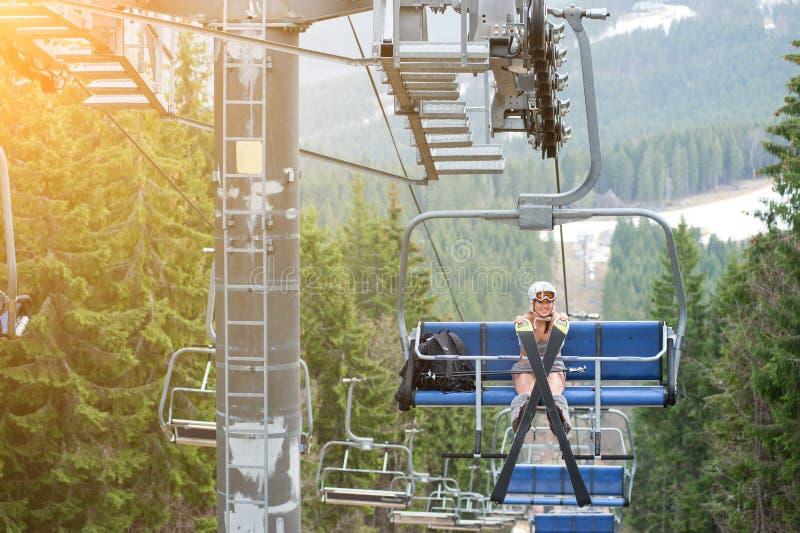 Le skieur féminin nu mignon a l'amusement sur le remonte-pente et monte jusqu'au dessus de la montagne avec le casque photographie stock libre de droits