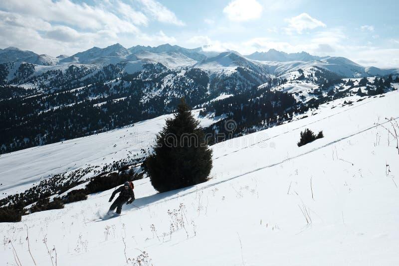 Le skieur parasitaire descend de la montagne à la lumière du soleil de matin photographie stock