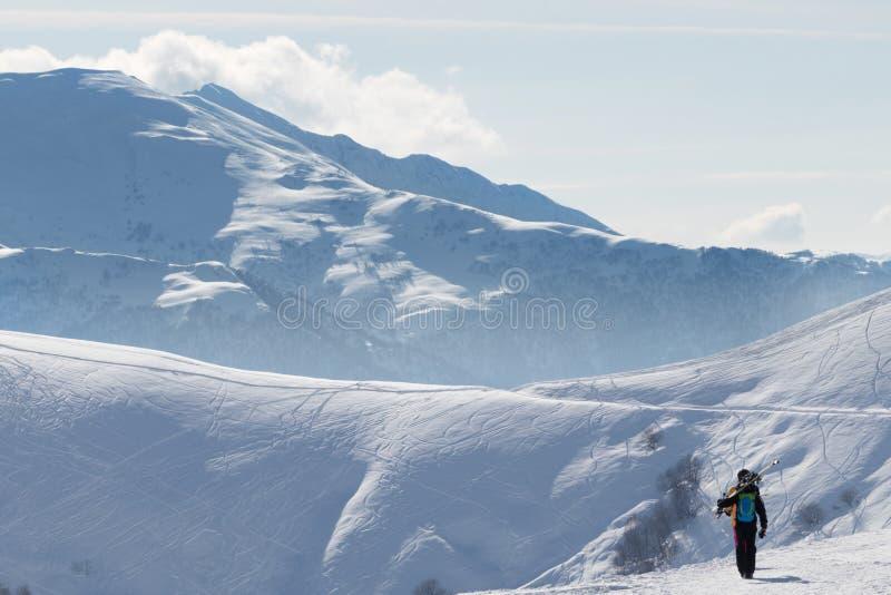 Le skieur va sur la route neigeuse au matin ensoleillé d'hiver photographie stock libre de droits