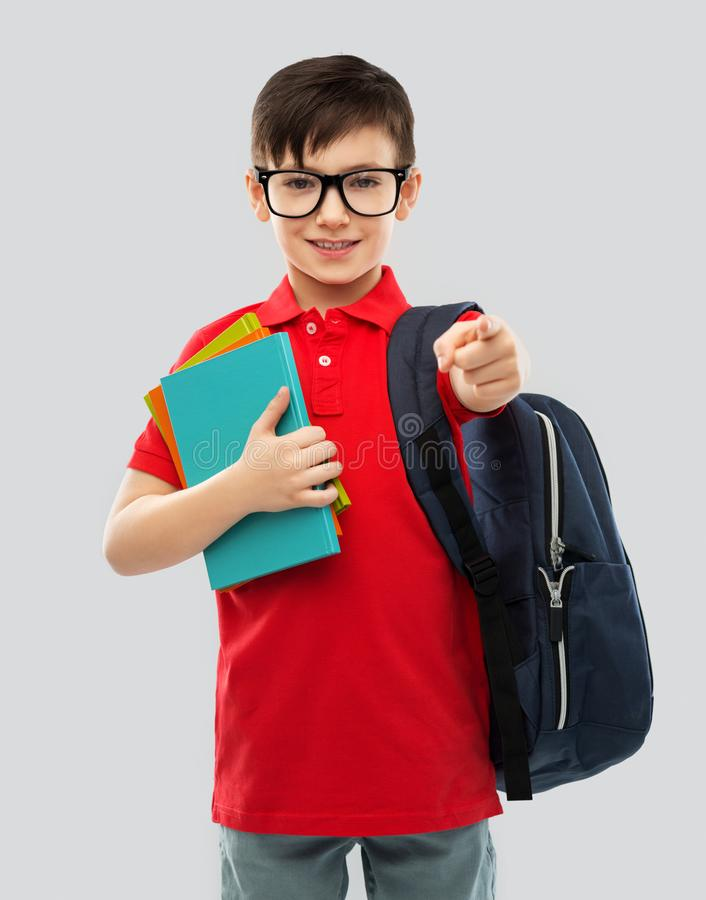 Le skolpojken i exponeringsglas med böcker och påsen royaltyfri bild