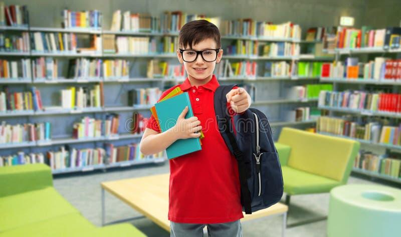 Le skolpojken i exponeringsglas med böcker på arkivet fotografering för bildbyråer