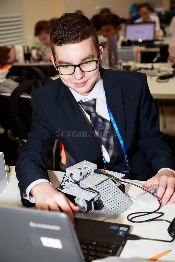 Le skolpojken som programmerar roboten på robotteknikkonkurrenser royaltyfri foto