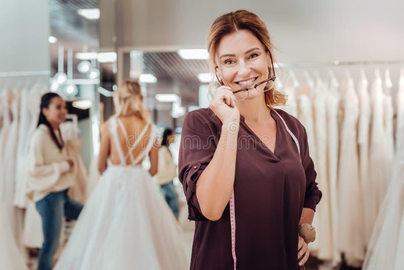 Le skräddaren som av tar hennes exponeringsglas som står i hennes, shoppa royaltyfria foton