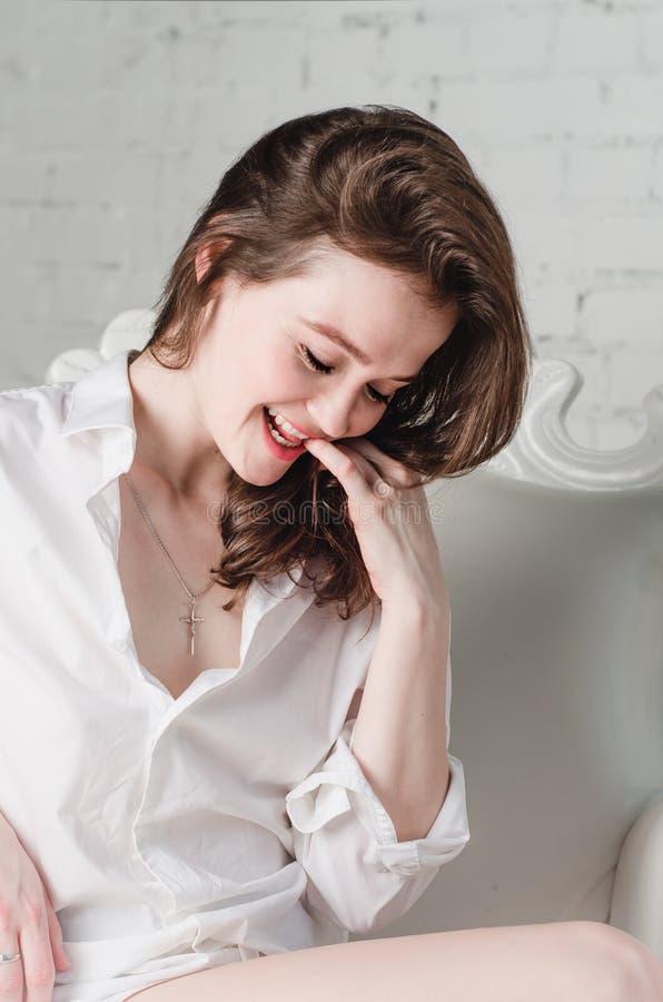 Le skratta kvinnaståenden - vila på stolsoffan i den vita skjortan för manpojkvän hemma i morgonlivsstil arkivfoton