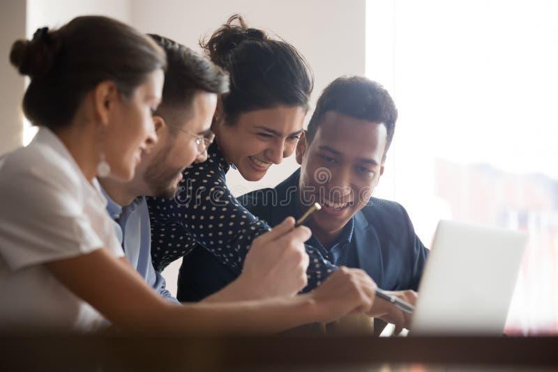 Le skrattar olika kollegor id?kl?ckning genom att anv?nda b?rbara datorn arkivfoto